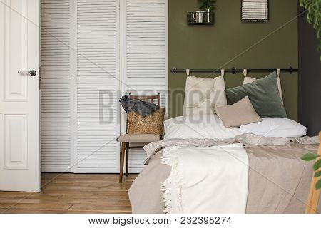 Interior Shot Of Bed With Cushions And Plaid In Simple And Cozy Design.