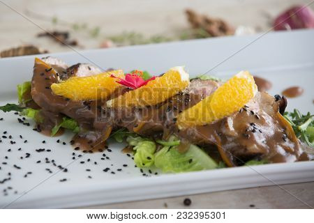 Roasted Duck Breast With Oranges And Orange Sauce On White Plate