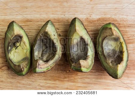 Four Pieces Of Roten Avocado On Wooden Background