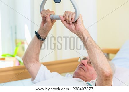 Senior man grabbing handle to get out of bed in nursing home