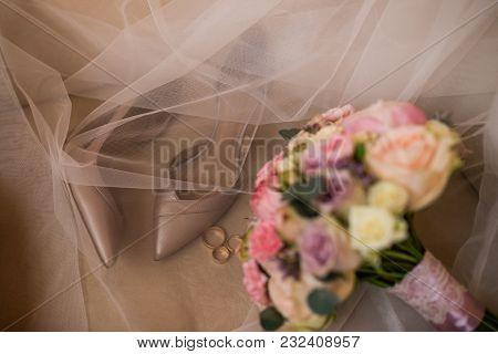 Golden Wedding Heels And Golden Rings In Focus On Brown Background Flowers Out Of Focus. Wed
