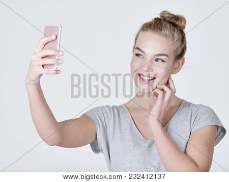 young beautiful caucasian girl makes selfies. Happy wonderful woman with mobile cell phone in hands