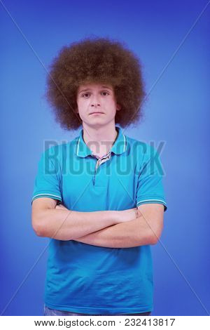 portrait of a young man with a funky hairstyle with arms crossed on blue background