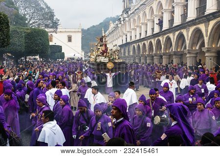 Antigua, Guatemala: March 18 2018: Float With Christ Statue Carried By Purple Robed Men At The Proce