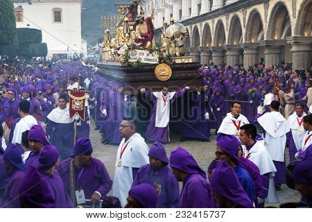 Antigua, Guatemala: March 18 2018: Float With Christ And The Cross Carried By Purple Robed Men At Th