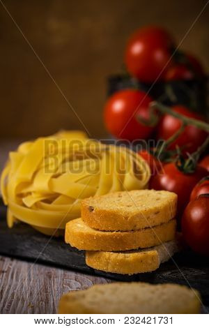 Few Pieces Of Bruschetta Next To Tagliatelle And Cherry Tomatoes