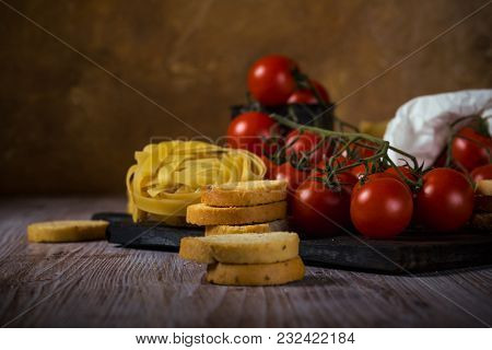 Red Cherry Tomatoes On Vintage Wooden Table With Tagliatelle And Bruschetta