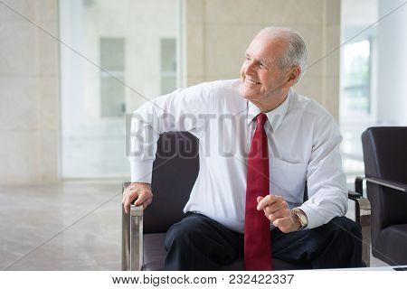 Portrait Of Cheerful Senior Caucasian Businessman Wearing Shirt And Tie Sitting In Armchair In Moder