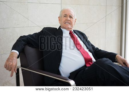 Portrait Of Senior Caucasian Executive Wearing Black Jacket And Necktie Sitting In Armchair And Grin