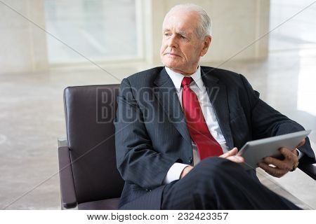 Portrait Of Pensive Senior Caucasian Executive Wearing Formal Suit Sitting In Armchair With Touchpad