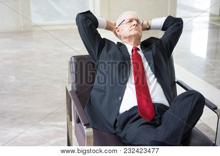 Portrait Of Senior Caucasian Businessman Wearing Glasses Resting In Armchair In Office. Business Bre