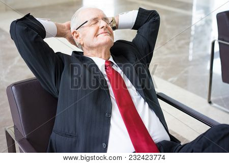 Portrait Of Sleepy Or Dreamy Senior Caucasian Businessman Wearing Glasses Resting In Armchair With H