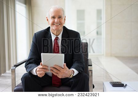 Portrait Of Successful Aged Caucasian Analyst Or Accountant With Touchpad And Calculator Looking At