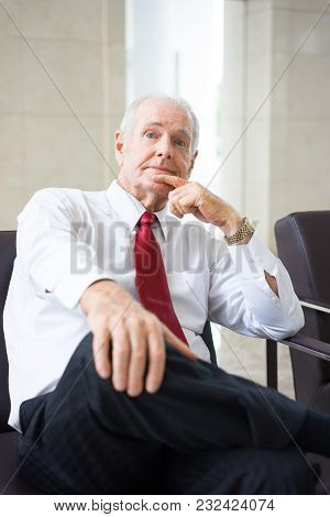 Portrait Of Senior Caucasian Leader Wearing Shirt And Tie Sitting In Armchair With Thoughtful Expres