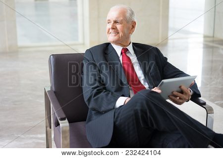 Portrait Of Positive Senior Caucasian Business Specialist Wearing Formal Suit Sitting In Armchair In