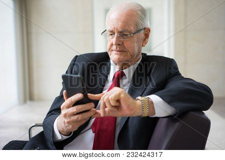 Portrait Of Serious Senior Caucasian Ceo Wearing Glasses Sitting In Armchair And Using Internet Or T