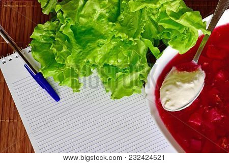 On The Table Are Lettuce, Notebook. Plate With Borsch And Spoon With Sour Cream