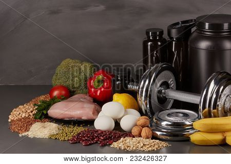Sports  nutrition (supplements), healthy food and dumbbells  on a black background. Fitness, bodybuilding, sport and healthy lifestyle concept.