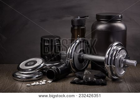 Sports  nutrition (supplements), sport accessories and dumbbells on a black background. Fitness, bodybuilding, sport and healthy lifestyle concept.