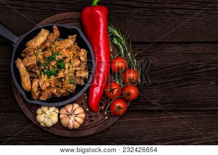 Top View Frying Pan With Roasted Pork And Garlic, Pepper, Rosemary And Tomatoes On Dark Wooden Backg