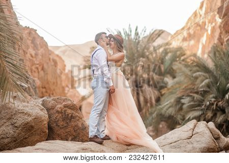 Bride In Long Dress And Groom In Sunglasses Stand And Hug In Canyon Against Background Of Rocks And