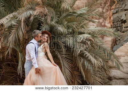 Groom Hugs And Kisses Of Bride In Long Dress On Background Of Palm Trees And Rocks.