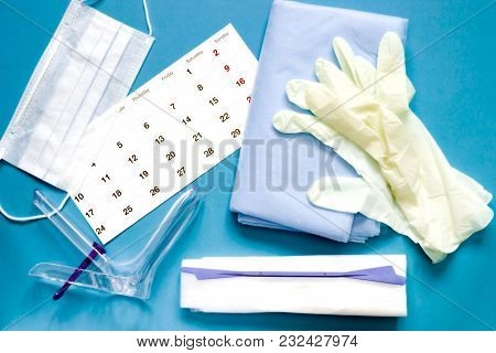An Overhead Photo Of The Vaginal Speculum, Napkin, Medicine Gloves, Calendar And Spatula. The Medica