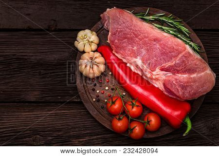 Top View Raw Pork Steak On Wooden Cutting Board With Red Chili Pepper, Peppercorn, Garlic, Tomatoes