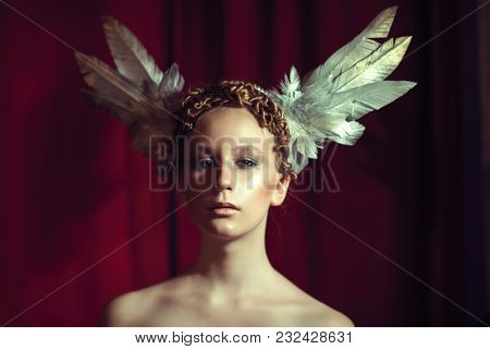 Red-haired Girl In A Rim In The Form Of Wings. Feather Headpiece