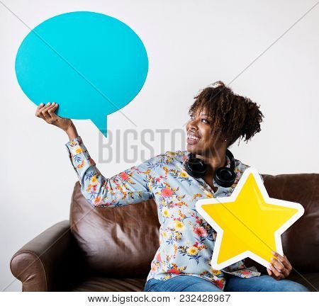 Happy African American holding copy space speech bubble and a star sign