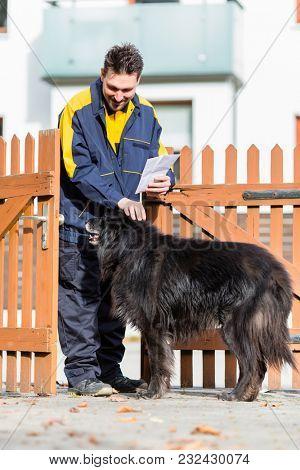 Big black dog welcoming the postman at garden gate