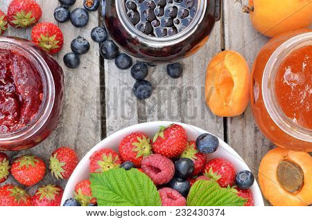 Bowl With Berries Fruit, Green Leaves And Jams - Strawberry, Apricot, Blueberry And Spilled Blackber