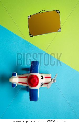 Flat Lay Design Of Travel Concept With Plane And Travel Bag On Blue And Pink Background.