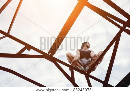 Risky Man Sitting On High Metal Construction, Outdoors