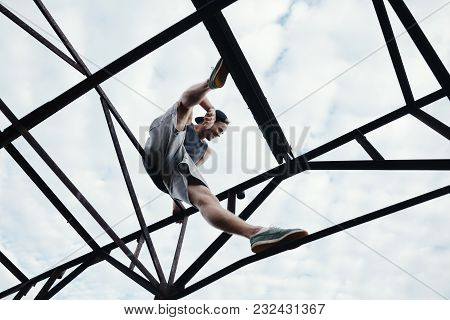Young Brave Man Sitting On The Top Of High Metal Construction, Outdoors