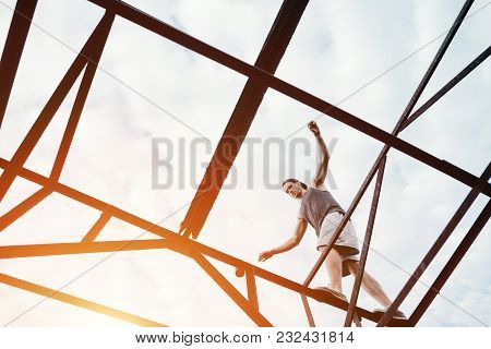 Young Brave Man Balancing On The Top Of High Metal Construction, Outdoors