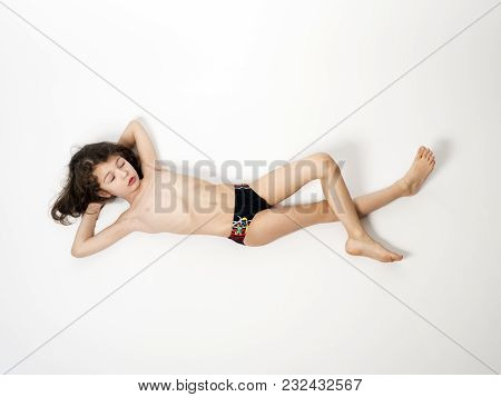 Adorable Little Boy In A Swimsuit Lying On The Floor, Isolated On A Light