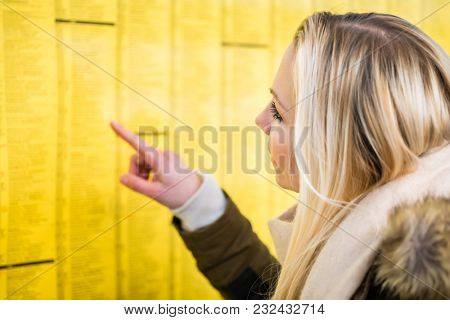 Woman reading time table in train station pinned on a board