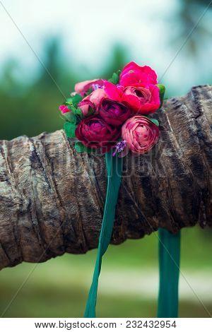 A Beautiful Wreath Of Flowers Lies On A Palm Tree.