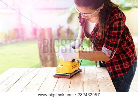 Womam Carpenter Working With Wood Electrical Sanding Machine