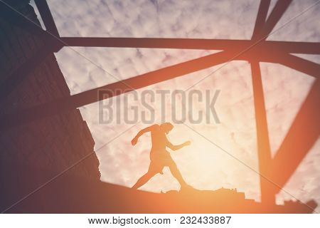 Silhouette Of Brave Man Walking On The Top Of Constructions At Sunset, Outdoors