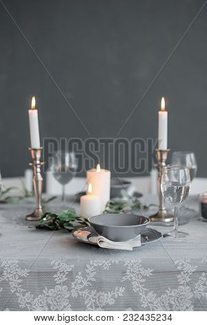 Wedding Or Festive Table Setting. Plates, Wine Glasses, Candles And Cutlery . Beautiful Arrangement.