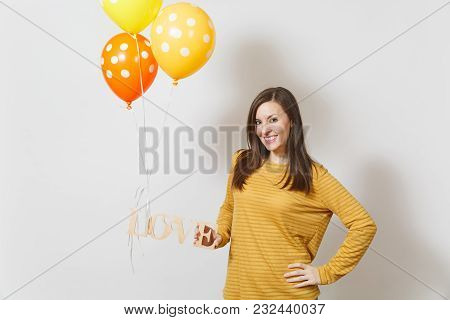 Beautiful Romantic Young Smiling Woman Holding Wooden Word Love, Yellow Orange Air Balloons On White