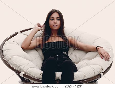 young woman sitting in comfortable round big chair