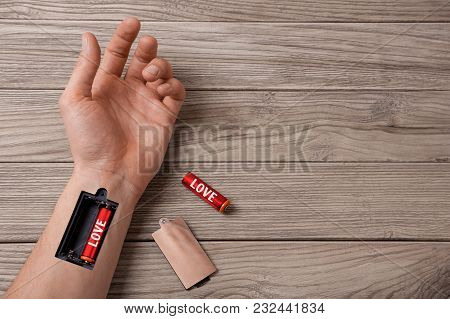 How To Recharge The Energy Of Love. Word Love Is Written On The Battery. Hand Of A Man With A Slot F