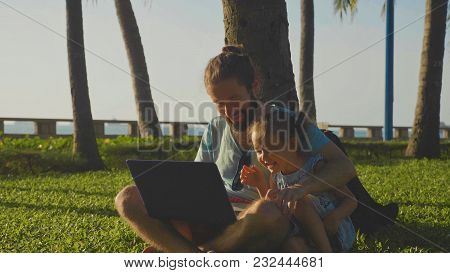 Father With Little Cute Girl Using Laptop Together At Park In Slow Motion.