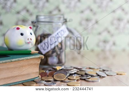 The Piggy Bank And A Green Pencil Are Placed On The Hardback With A Pile Of Coins On A Wooden Table.