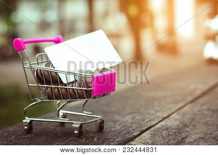 Saving Money Concept With Money On Cart And White Card Business On Abstract Sunset Background