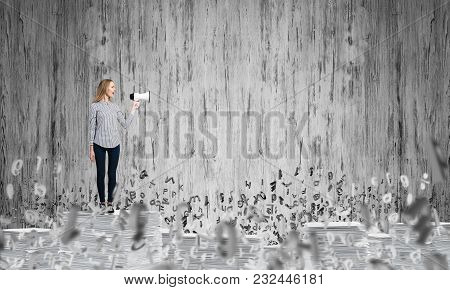 Woman In Casual Clothing Standing Among Flying Letters With Speaker In Hand And With Grey Wall On Ba