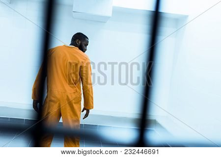 Back View Of African American Prisoner In Prison Cell